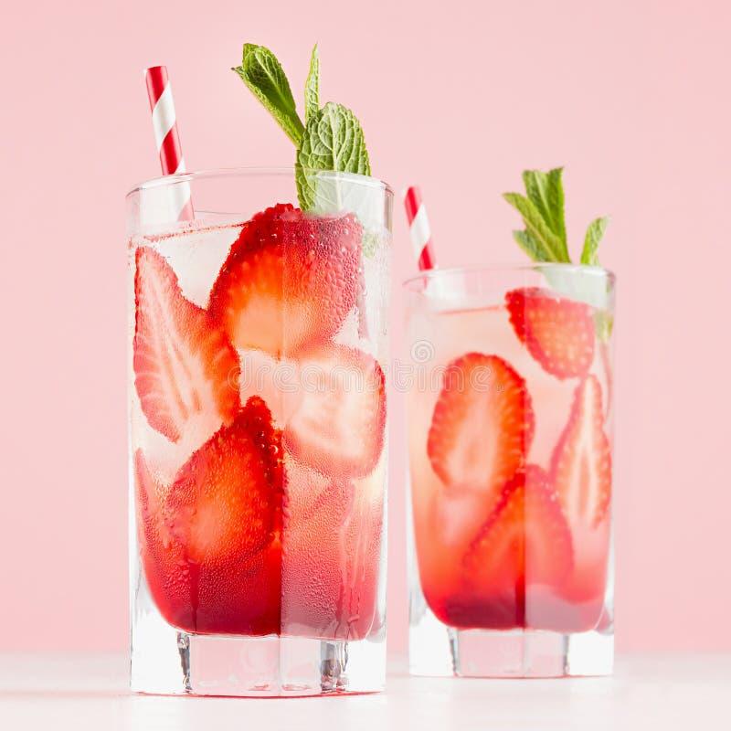 Холодный здоровый напиток плода с клубникой, зеленой мятой, льдом, соломой в misted стекле в розовом интерьере на белом деревянно стоковое фото