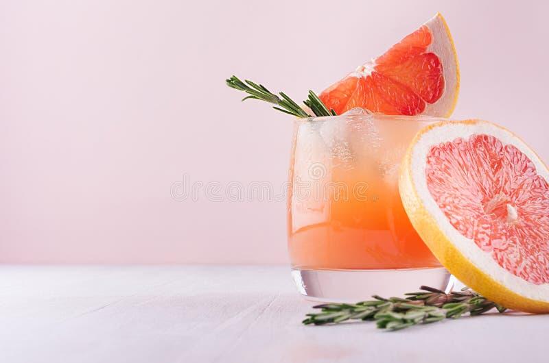 Холодный лимонад свежего сока грейпфрута, спирт и украшенные кубы льда отрезают розмариновое масло цитруса и хворостины на розово стоковая фотография