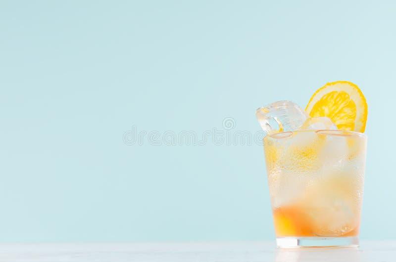 Холодный напиток апельсинов во влажной стопке с частями апельсином, кубами льда на элегантной мягкой салатовой предпосылке, космо стоковое изображение rf