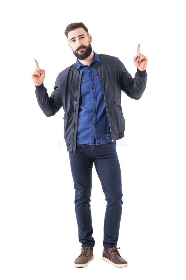 Холодный расслабленный бородатый человек в куртке голубого бомбардировщика указывая палец вверх выше и смотря камеру стоковые фото