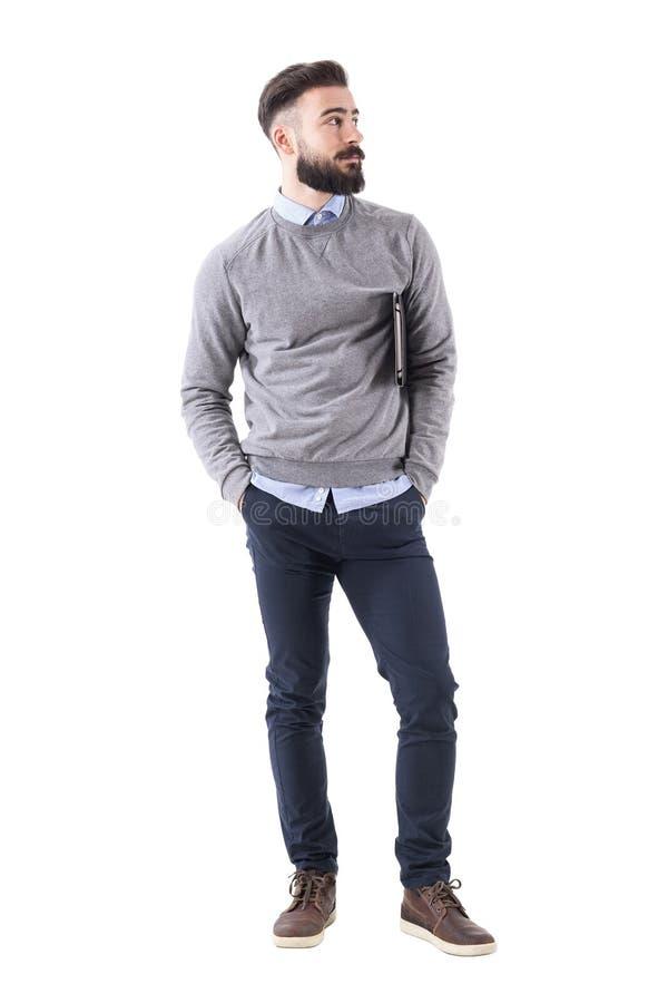Холодный расслабленный современный тысячелетний парень при тетрадь стоя и смотря прочь стоковые фото