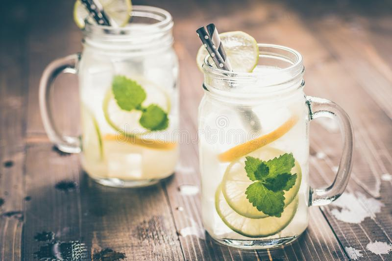 Холодный свежий лимонад коктейля Mojito с листьями льда, лимона и мяты в опарнике каменщика стоковое изображение