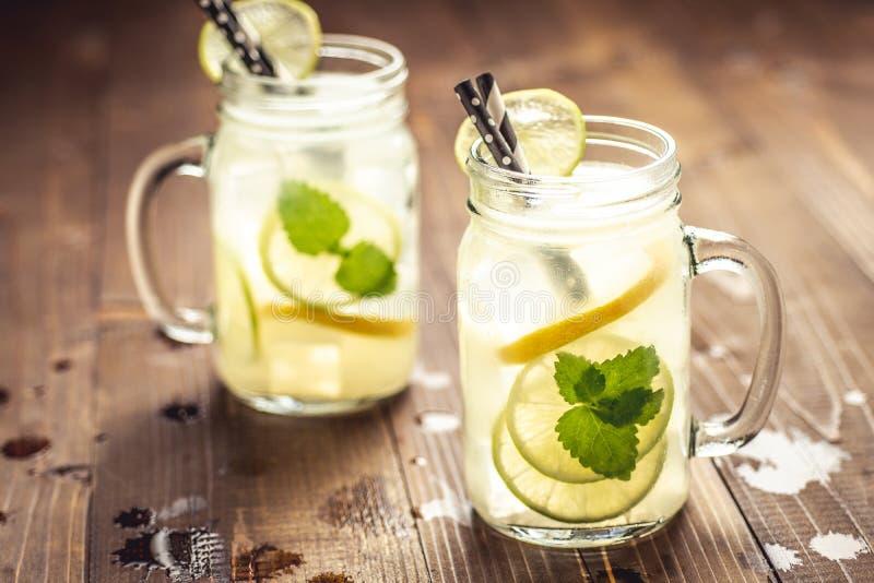 Холодный свежий лимонад коктейля Mojito с листьями льда, лимона и мяты в опарнике каменщика стоковое фото rf