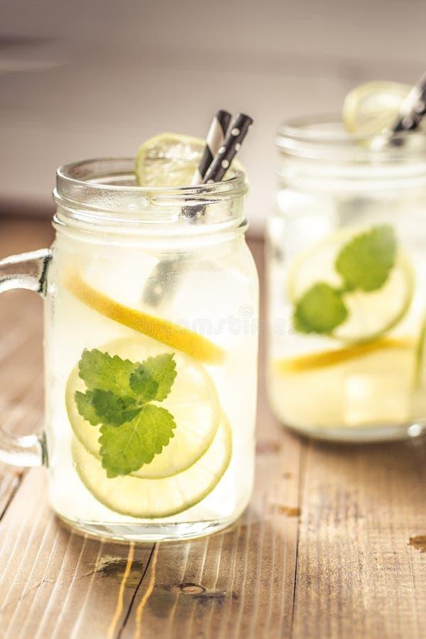 Холодный свежий лимонад коктейля Mojito с листьями льда, лимона и мяты в опарнике каменщика стоковые фотографии rf