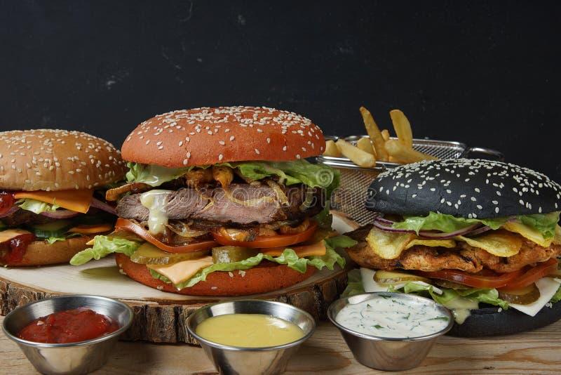 3 холодных бургера и различных соусы к французским фраям стоковое фото