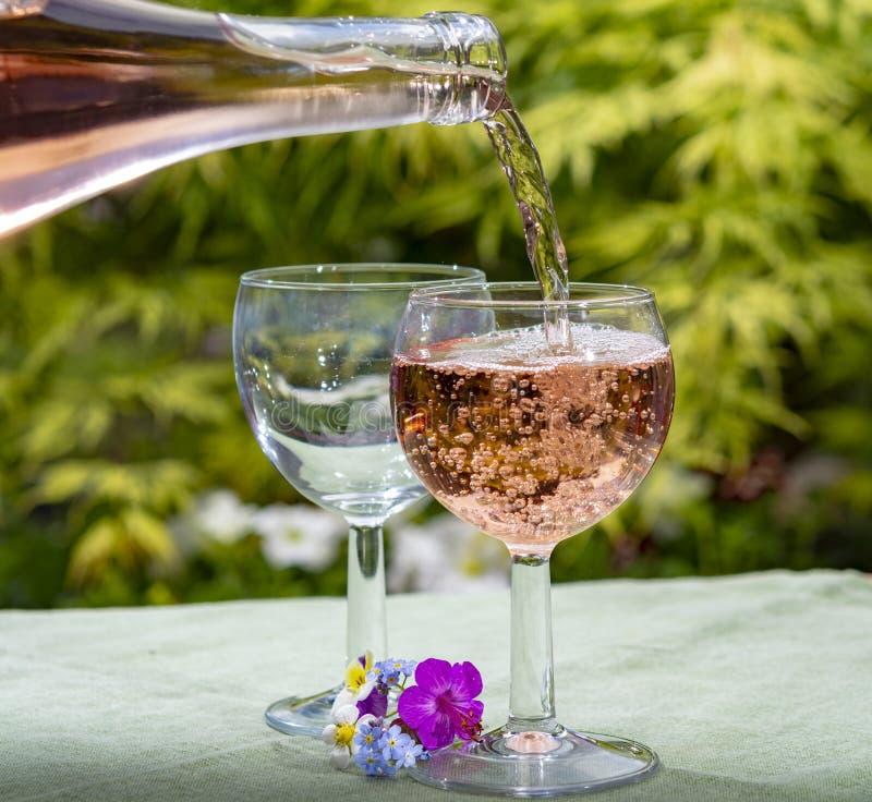 Холод официанта лить розовое вино в стеклах во дне лета солнечном в цвести саде стоковые изображения rf