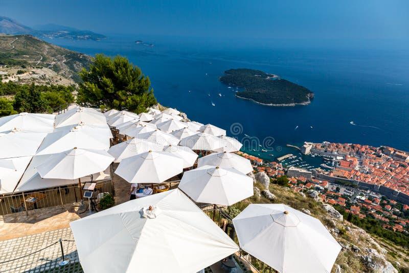 Хорватия dubrovnik Взгляд сверху над рестораном с зонтиками солнца и старым городком ниже стоковая фотография rf