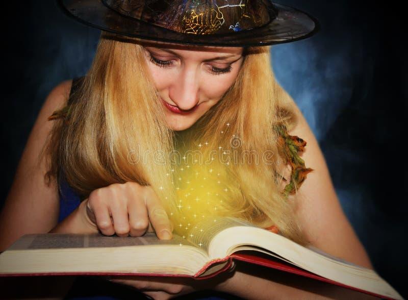 Хорошая ведьма в шляпе читает магические заклинания в книге на предпосылке тумана стоковые изображения rf