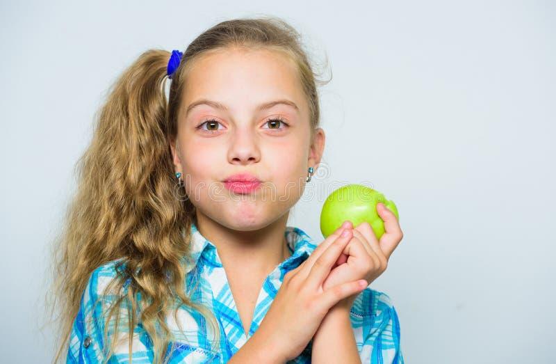 Хорошее питание необходимо к хорошим здоровьям Девушка ребенк ест зеленый плодоовощ яблока Питательное содержание яблока витамин стоковое фото rf