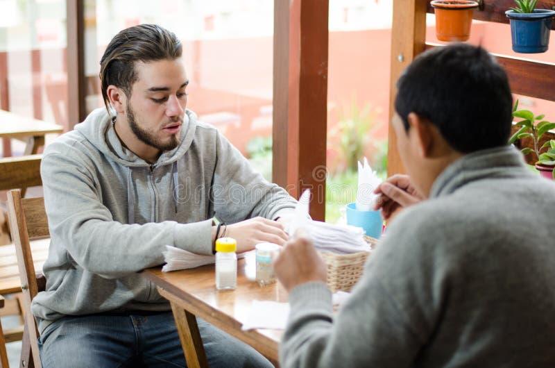 Хорошее смотря молодые люди исправляя таблица с салфетками стоковое изображение