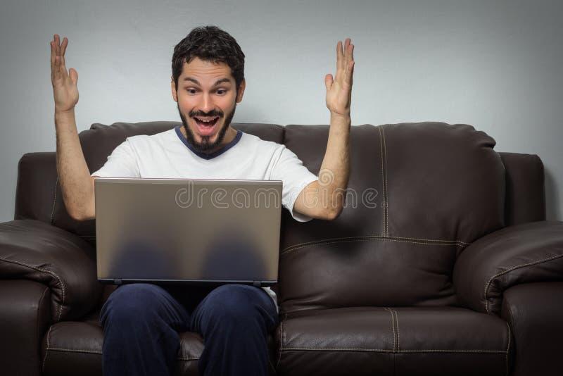 Хорошие новости чтения человека в его компьтер-книжке стоковые изображения rf