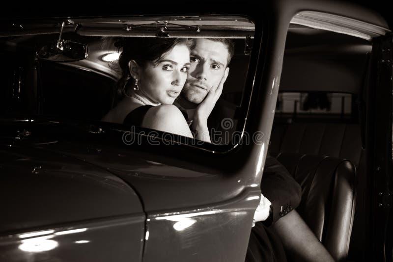 Хорошие смотря сексуальные пары, красивый человек в костюме, красивая женщина в красном платье, открытый обнимать в винтажном авт стоковые фото