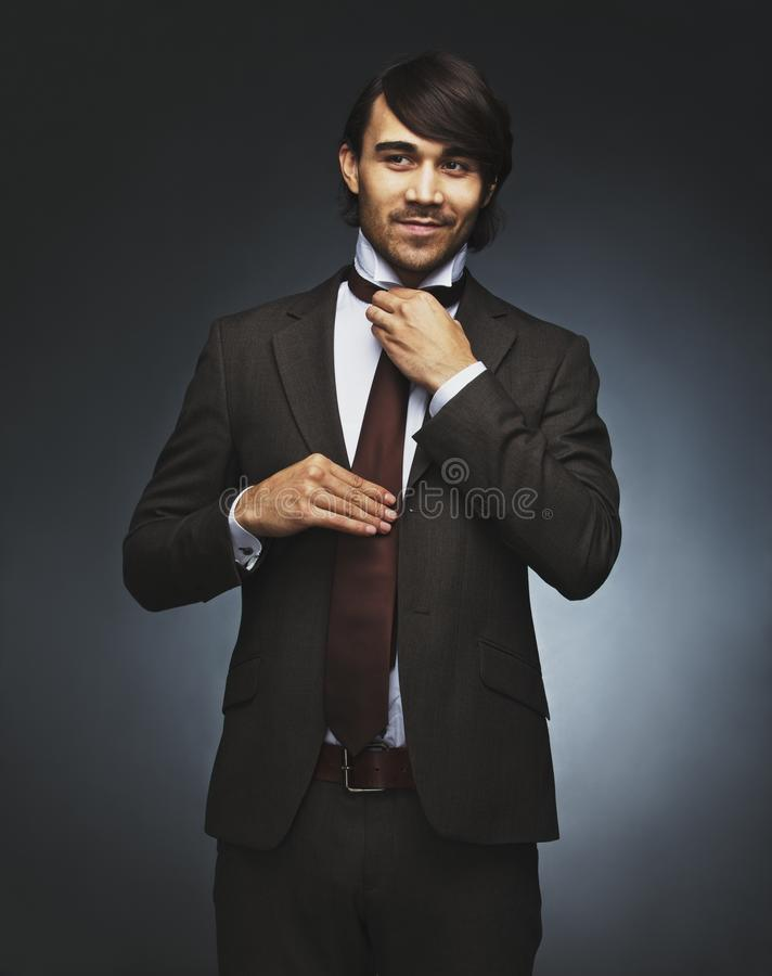 Хороший смотря человек в костюме регулируя его галстук стоковое фото
