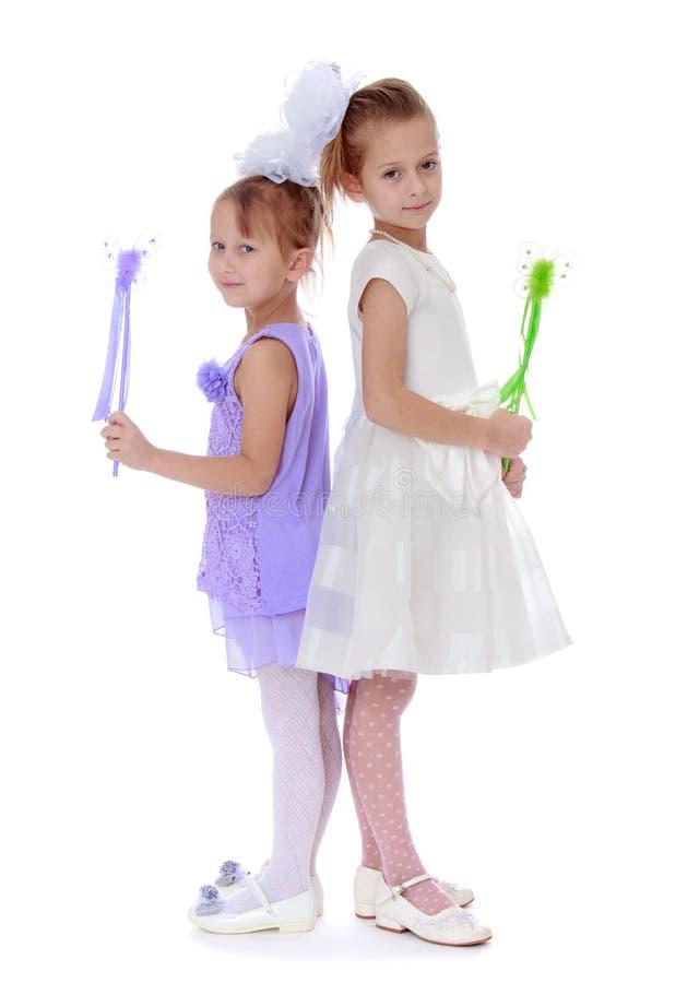 2 хорошо одетая девушка держа волшебную палочку стоковая фотография