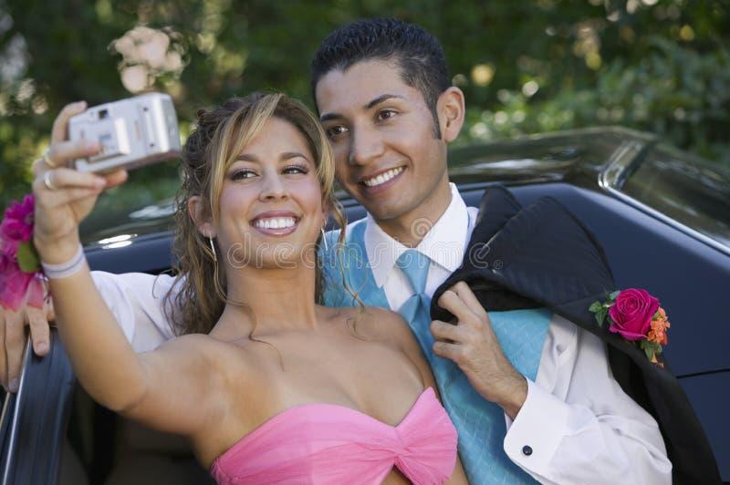 Хорошо одетые подростковые пары фотографируя вне автомобиля стоковые изображения rf