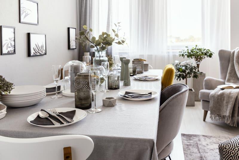 Хорошо положенная таблица с плитами и стеклами в сером интерьере столовой Реальное фото стоковые изображения