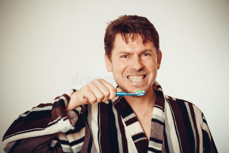 Хорош-humored человек в тонизированных зубах купального халата чистя щеткой, стоковые изображения rf