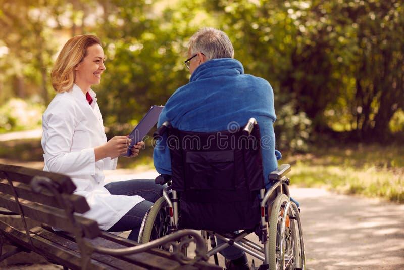 Хоспис проверяя вверх по истории пациента в кресло-коляске стоковое изображение