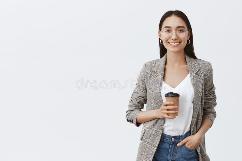 Хотеть хватать кофе Портрет расслабленной и уверенной европейской женщины с темными волосами и стеклами, держа руку в кармане стоковые фотографии rf