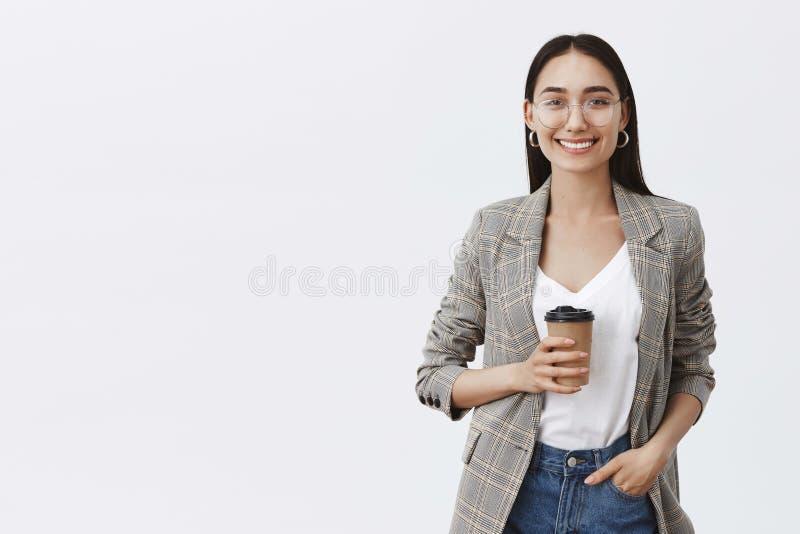 Хотеть хватать кофе Портрет расслабленной и уверенной европейской женщины с темными волосами и стеклами, держа руку в кармане стоковое фото