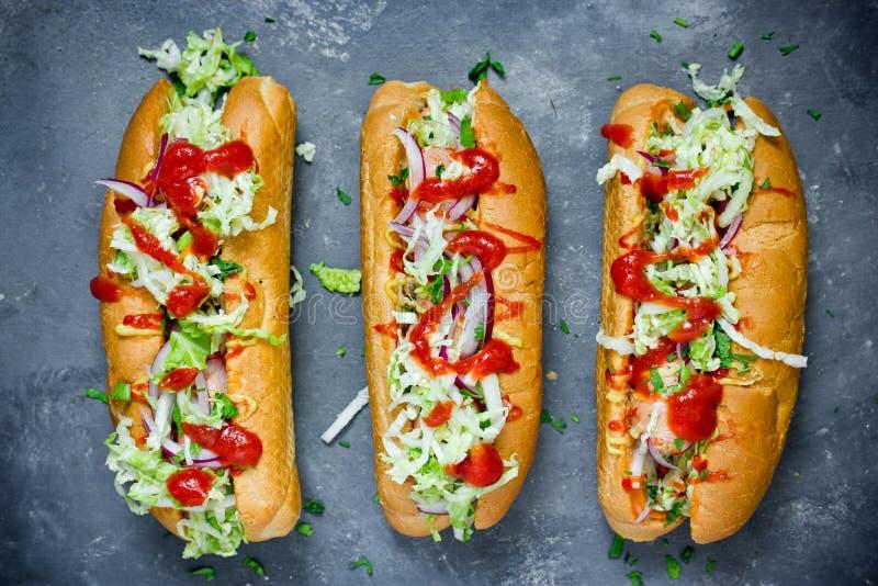 Хот-дог с колбасой, огурцом, капустой и томатным соусом стоковая фотография