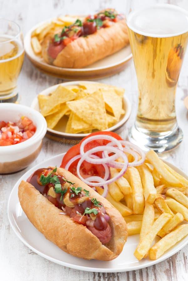 хот-доги с французскими фраями, пивом и закусками, вертикальными стоковое изображение