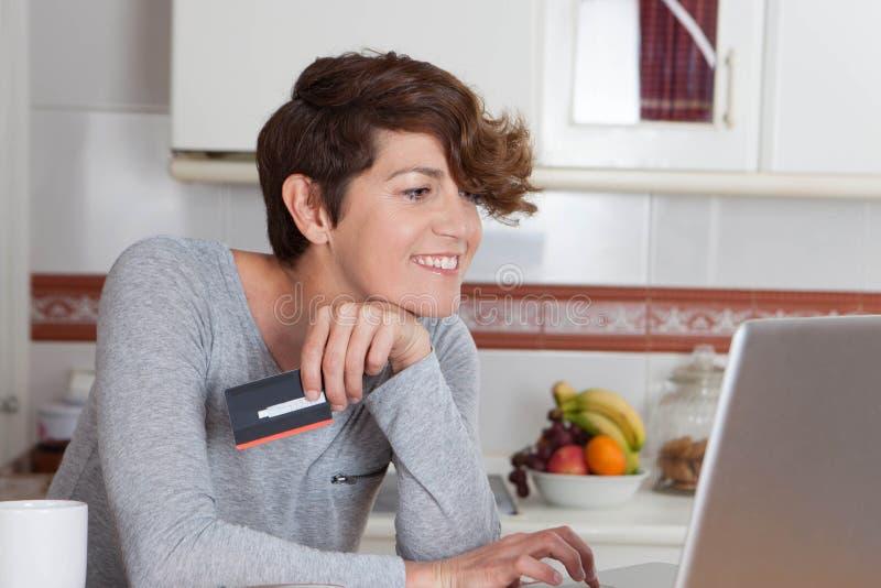 Ходить по магазинам женщины онлайн с кредитной карточкой стоковое изображение rf