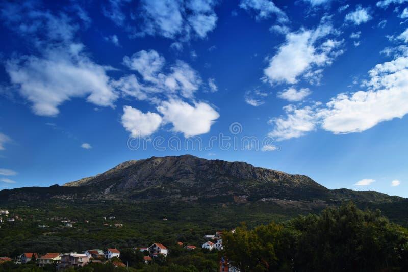 Холм среди облаков и долины заполнил с домами стоковые изображения rf