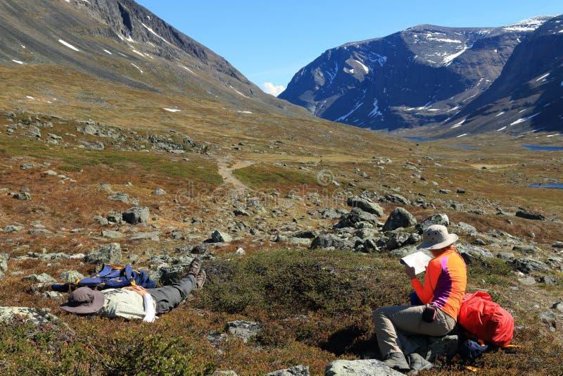 Ходоки в ярко покрашенных внешних остатках шестерни и прочитанные карте на тропе Kungsleden в Швеции стоковые изображения