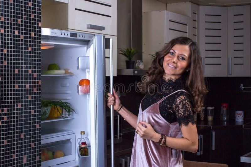 Холодильник отверстия женщины на ноче стоковое изображение rf