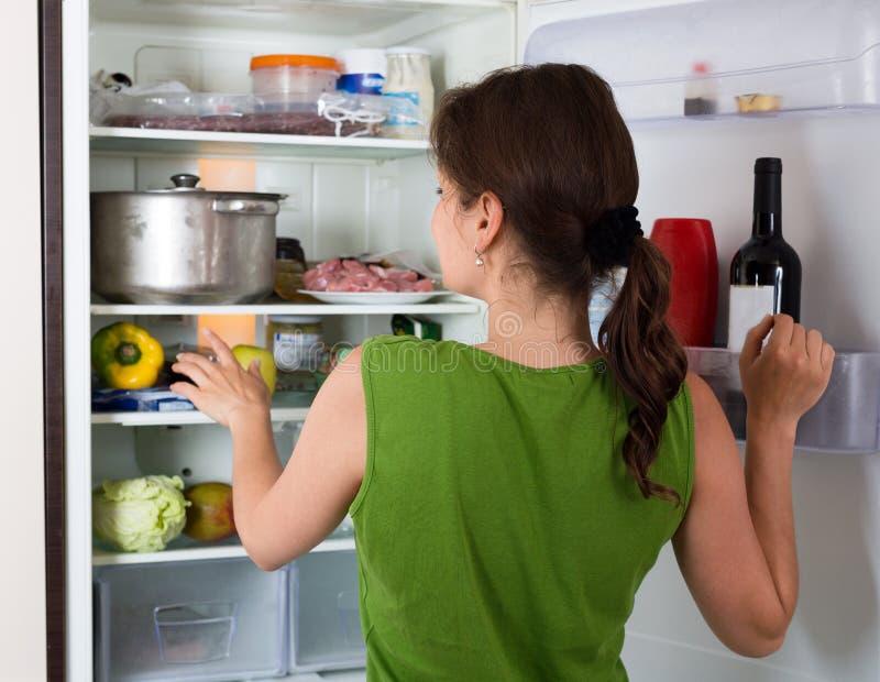 Холодильник отверстия женщины с едой стоковая фотография