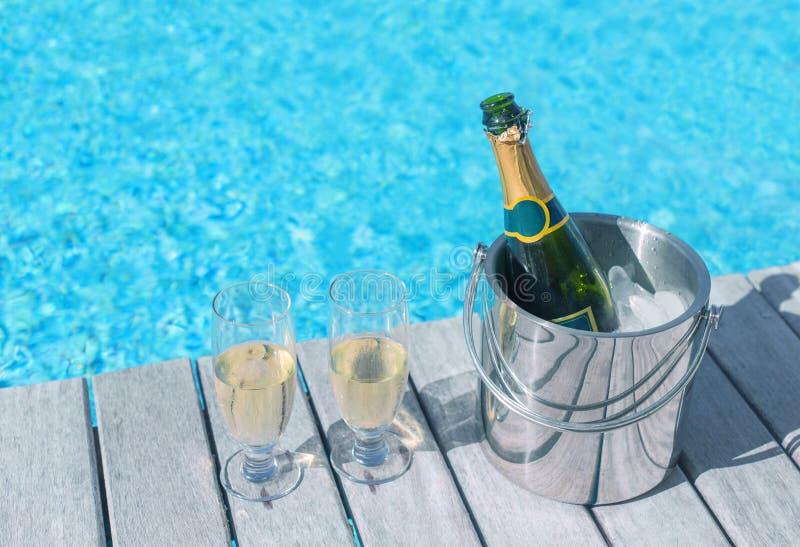 Холодная бутылка шампанского в ведре льда и 2 стеклах шампанского на палубе бутылкой в ведре и 2 стеклах шампанского стоковое изображение