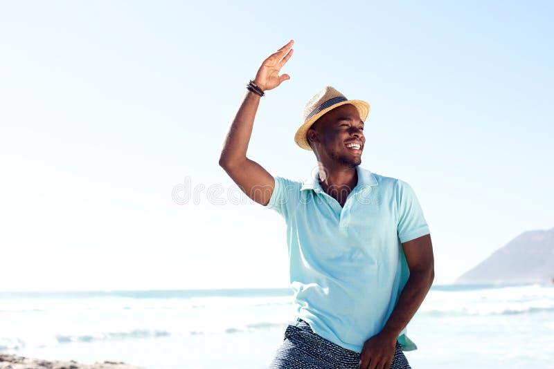 Холодные молодые африканские танцы человека на пляже стоковое фото rf