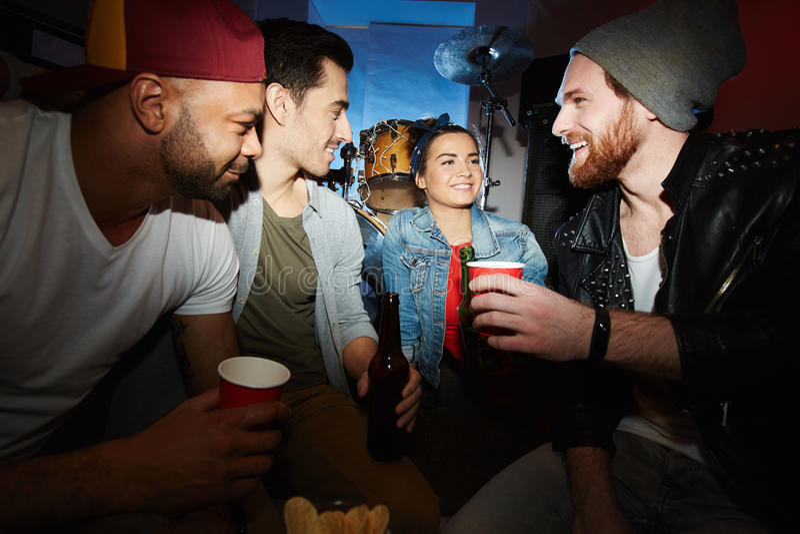 Холодные друзья охлаждая с пивом на партии ночного клуба стоковые фото