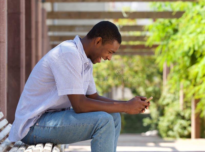 Холодный Афро-американский парень смотря сотовый телефон стоковое изображение rf