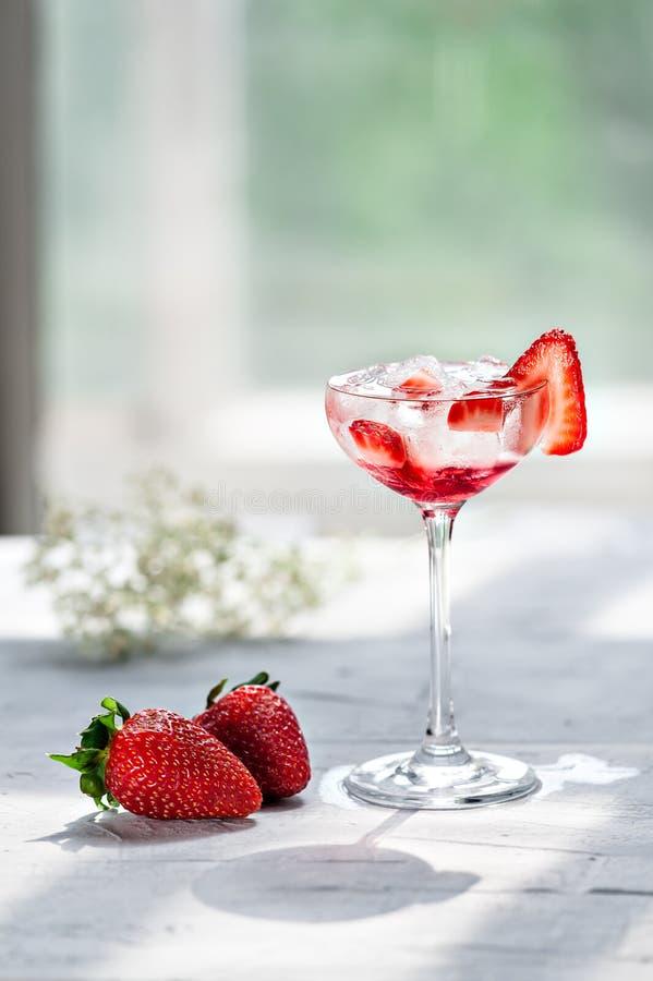 Холодный коктеиль с водочкой, сиропом клубники, свежими клубниками и задавленным льдом в стеклах на светлой предпосылке стоковые фото