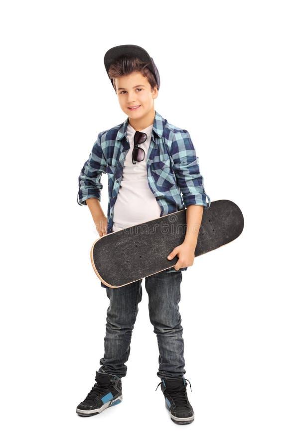 Холодный маленький ребенок держа скейтборд стоковые изображения
