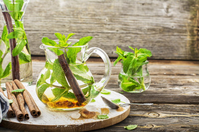 Холодный освежая морокканский чай с циннамоном и мятой в высокорослом графинчике на простой деревянной предпосылке с желтым сахар стоковые изображения