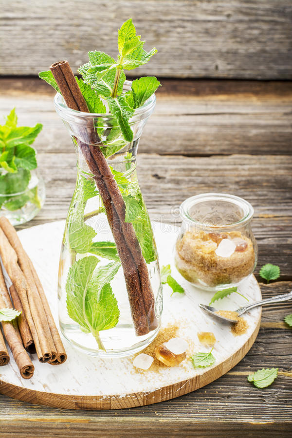 Холодный освежая морокканский чай с циннамоном и мятой в высокорослом графинчике на простой деревянной предпосылке с желтым сахар стоковые фото