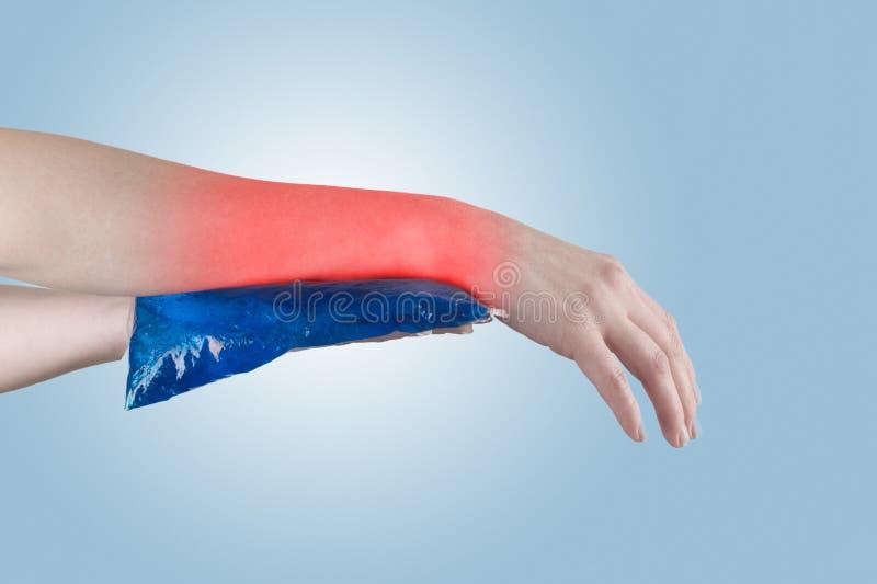 Холодный пакет геля на вздутом ушибая запястье руки стоковое фото
