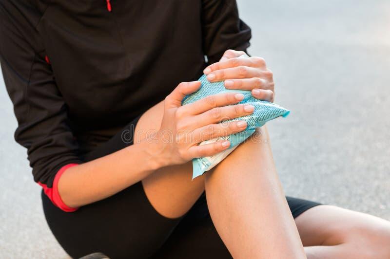 Холодный пакет геля на вздутом ушибая колене стоковое фото rf
