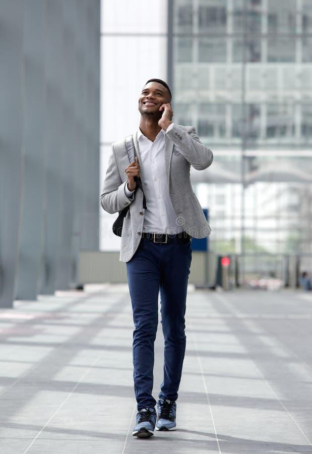 Холодный парень идя и разговаривая с мобильным телефоном стоковая фотография rf
