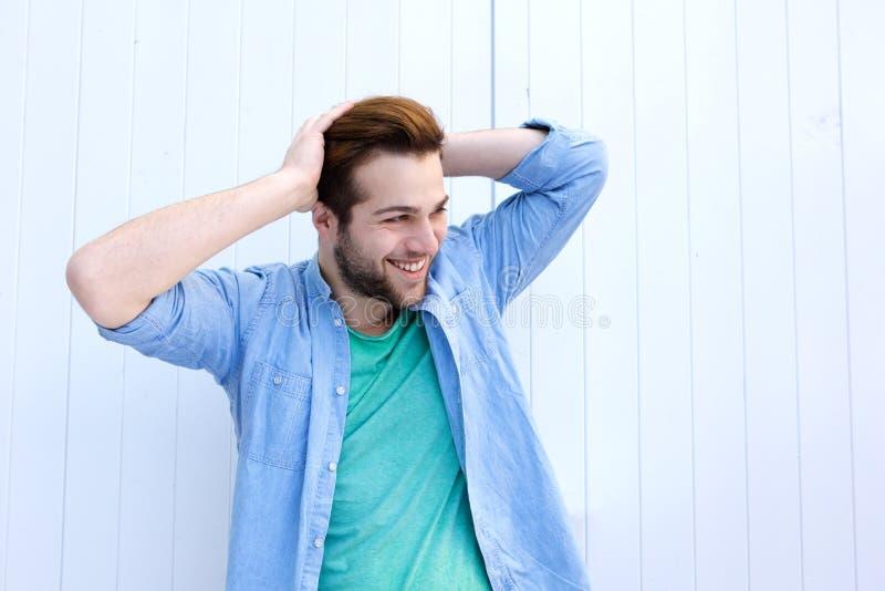 Холодный парень усмехаясь с рукой в волосах стоковые изображения rf