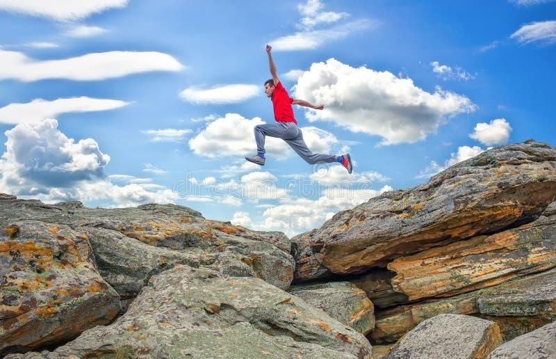 Ход спортсмена, скача над утесами в горной области стоковое изображение rf