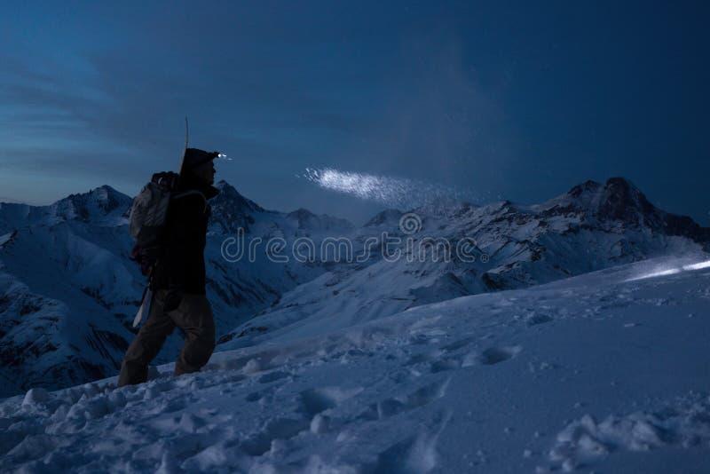 Храбрый человек путешественника совершает лыжный поход на высокой горе на ноче Профессиональный snowboarder освещает путь с headl стоковые изображения