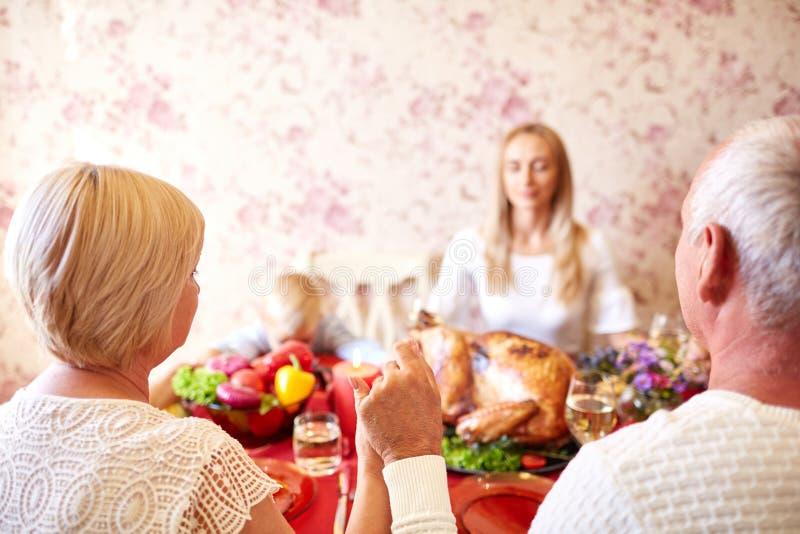 Христианская семья моля на обедающем благодарения на светлой предпосылке Признательная концепция стоковые фотографии rf