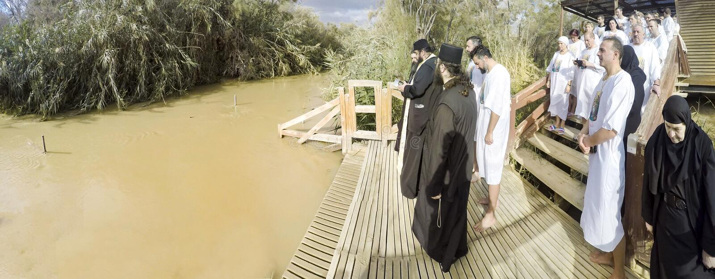 Христианские паломники во время массовой церемонии крещения на реке Иордан стоковое изображение