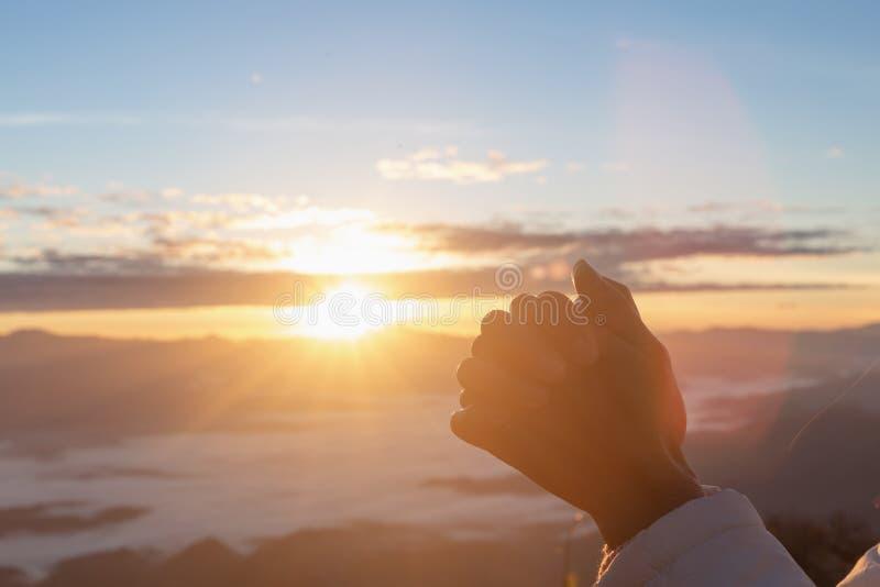 Христианские руки женщины моля к богу на предпосылке горы с восходом солнца утра Женщина молит для бога благословение к желать им стоковые изображения
