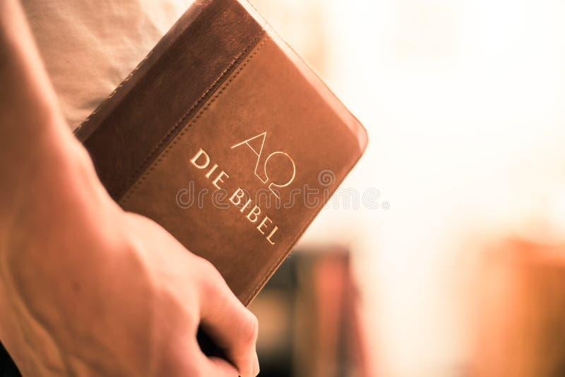 Христианский проповедник: Молодой человек держит библию, моля стоковая фотография rf