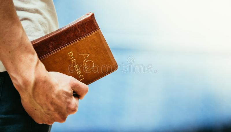 Христианский проповедник: Молодой человек держит библию, моля стоковое изображение rf
